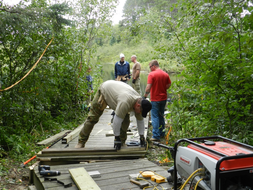 Volunteers from the 450 Tactical Helicopter Squadron at Garrison Petawawa repair the boardwalks on the PRF Water Trail on August 7, 2013.